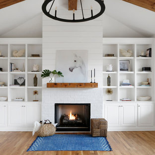 Mittelgroßes, Offenes Landhausstil Wohnzimmer mit weißer Wandfarbe, hellem Holzboden, Kamin, Kaminumrandung aus Backstein, Wand-TV und buntem Boden in Nashville