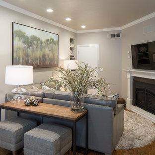 Ejemplo de sala de estar cerrada, moderna, pequeña, con paredes grises, suelo de madera en tonos medios, chimenea tradicional y televisor colgado en la pared