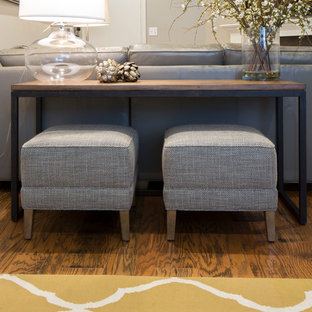 Ejemplo de sala de estar cerrada, minimalista, pequeña, con paredes grises, suelo de madera en tonos medios, chimenea tradicional y televisor colgado en la pared