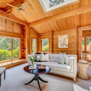 シアトルの大きいラスティックスタイルのおしゃれな独立型ファミリールーム (カーペット敷き、薪ストーブ、石材の暖炉まわり、グレーの床) の写真