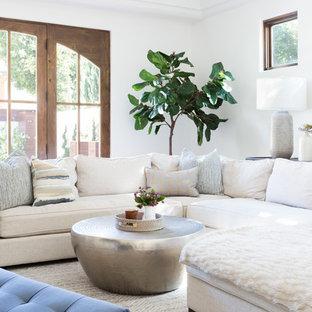 Cette photo montre une grande salle de séjour méditerranéenne ouverte avec un mur blanc, un sol en bois brun, une cheminée d'angle, un manteau de cheminée en béton et un téléviseur fixé au mur.
