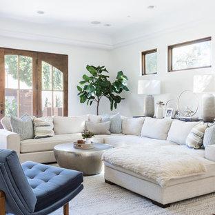 Großes Mediterranes Wohnzimmer mit weißer Wandfarbe, braunem Holzboden und braunem Boden in Los Angeles