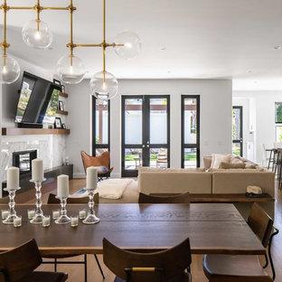 Idéer för stora funkis allrum med öppen planlösning, med vita väggar, mellanmörkt trägolv, en standard öppen spis, en spiselkrans i sten, beiget golv, en hemmabar och en väggmonterad TV