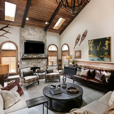Family room - huge rustic open concept family room idea in New York with beige walls, a standard fireplace, a stone fireplace and a wall-mounted tv