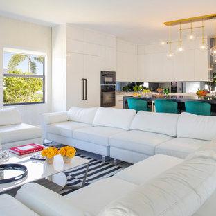 Ispirazione per un grande soggiorno minimalista aperto con sala giochi, pareti beige, pavimento in marmo, camino sospeso, cornice del camino in intonaco, TV a parete e pavimento bianco