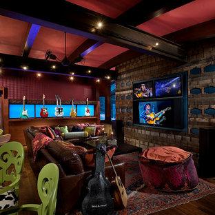 Ejemplo de sala de estar con rincón musical cerrada, ecléctica, grande, con pared multimedia, suelo marrón, paredes multicolor y suelo de madera oscura