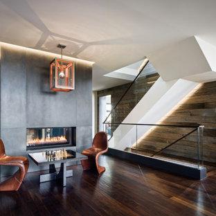 サンフランシスコの大きいコンテンポラリースタイルのおしゃれなファミリールーム (ゲームルーム、ベージュの壁、濃色無垢フローリング、両方向型暖炉、コンクリートの暖炉まわり、テレビなし、茶色い床) の写真