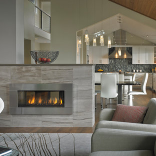 Example of a large minimalist open concept medium tone wood floor and brown floor family room design in Seattle with white walls, a two-sided fireplace, a stone fireplace and a wall-mounted tv