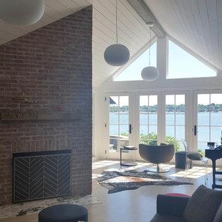 ニューヨークの中くらいのビーチスタイルのおしゃれなオープンリビング (ミュージックルーム、白い壁、淡色無垢フローリング、標準型暖炉、レンガの暖炉まわり、据え置き型テレビ) の写真