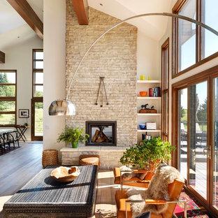 Imagen de sala de estar con biblioteca abierta, campestre, extra grande, sin televisor, con paredes blancas, suelo de madera clara, chimenea de doble cara y marco de chimenea de piedra