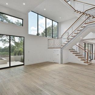 Ispirazione per un ampio soggiorno classico aperto con pareti bianche, pavimento in legno massello medio, camino classico e cornice del camino in pietra