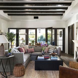 Diseño de sala de estar abierta, mediterránea, con paredes blancas, suelo de madera oscura, chimenea tradicional y pared multimedia