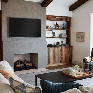 Design ideas for a medium sized mediterranean family and games room in San Francisco with white walls, medium hardwood flooring, a standard fireplace, a concrete fireplace surround, a wall mounted tv and brown floors.