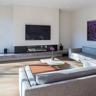 トロントの大きいモダンスタイルのおしゃれなファミリールーム (白い壁、無垢フローリング、横長型暖炉、壁掛け型テレビ、金属の暖炉まわり、茶色い床) の写真