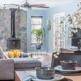タンパのエクレクティックスタイルのおしゃれなファミリールーム (青い壁、無垢フローリング、据え置き型テレビ、薪ストーブ、石材の暖炉まわり、茶色い床) の写真