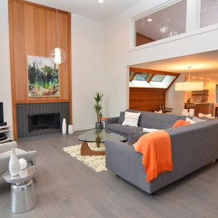Idee per un ampio soggiorno minimalista aperto con pareti bianche, camino lineare Ribbon, cornice del camino in legno, porta TV ad angolo e pavimento in legno massello medio
