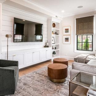 Ejemplo de sala de estar con biblioteca clásica renovada, sin chimenea, con paredes grises, suelo de madera clara y pared multimedia