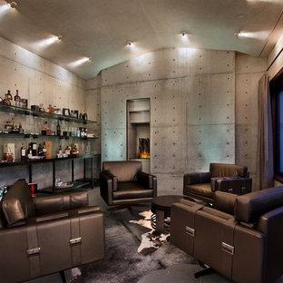 ロサンゼルスの中サイズのインダストリアルスタイルのおしゃれなファミリールーム (ホームバー、グレーの壁、標準型暖炉、コンクリートの暖炉まわり) の写真