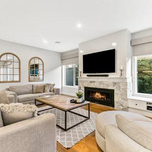 Diseño de sala de estar abierta, tradicional renovada, grande, con paredes blancas, chimenea tradicional, marco de chimenea de piedra, televisor colgado en la pared, suelo de madera en tonos medios y suelo amarillo