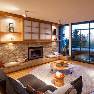 バンクーバーの中サイズのコンテンポラリースタイルのおしゃれな独立型ファミリールーム (白い壁、竹フローリング、標準型暖炉、石材の暖炉まわり、埋込式メディアウォール、ベージュの床) の写真
