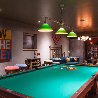 Modelo de sala de juegos en casa cerrada, bohemia, pequeña, sin chimenea, con suelo de corcho, televisor colgado en la pared y paredes grises