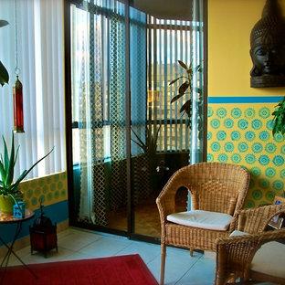 Ejemplo de sala de estar con biblioteca cerrada, bohemia, pequeña, con paredes amarillas y suelo de baldosas de cerámica