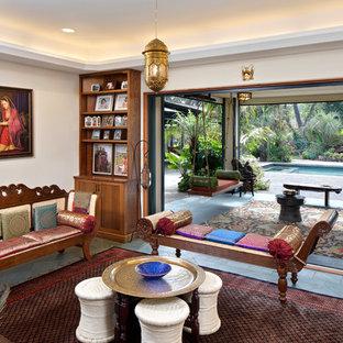 Diseño de sala de estar con biblioteca cerrada, mediterránea, de tamaño medio, sin televisor, con paredes beige, suelo de baldosas de porcelana, estufa de leña y suelo verde