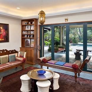 Modelo de sala de estar con biblioteca cerrada, mediterránea, de tamaño medio, sin televisor, con paredes beige, suelo de baldosas de porcelana, estufa de leña y suelo verde