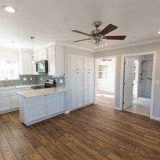 Kleines, Abgetrenntes Klassisches Wohnzimmer ohne Kamin mit grauer Wandfarbe, Laminat, Wand-TV und braunem Boden in San Francisco