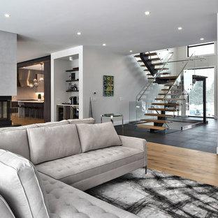 トロントの広いコンテンポラリースタイルのおしゃれなオープンリビング (グレーの壁、淡色無垢フローリング、コンクリートの暖炉まわり、壁掛け型テレビ、両方向型暖炉、ベージュの床) の写真