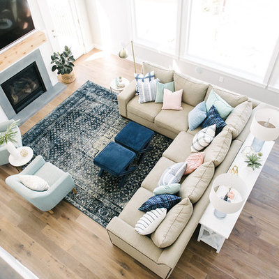 Inspiration for a large transitional medium tone wood floor family room remodel in Salt Lake City with gray walls, a standard fireplace and a wall-mounted tv