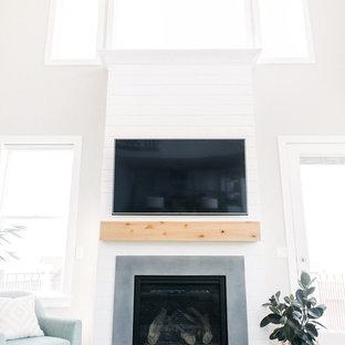 ソルトレイクシティの大きいトランジショナルスタイルのおしゃれなファミリールーム (グレーの壁、無垢フローリング、標準型暖炉、コンクリートの暖炉まわり、壁掛け型テレビ) の写真