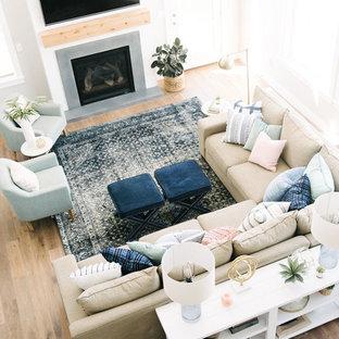 Foto di un grande soggiorno tradizionale aperto con pareti grigie, pavimento in legno massello medio, camino classico, cornice del camino in cemento e TV a parete