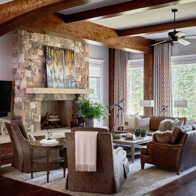 Inspiration for a rustic open concept medium tone wood floor family room remodel in Raleigh with gray walls, a standard fireplace, a stone fireplace and a wall-mounted tv