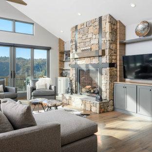 Idée de décoration pour une salle de séjour tradition avec un sol en bois brun, une cheminée standard, un manteau de cheminée en pierre, un sol marron, un mur blanc et un téléviseur fixé au mur.