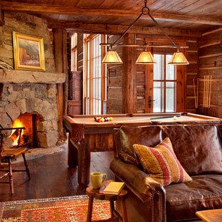 Esempio di un soggiorno stile rurale di medie dimensioni e aperto con sala giochi, pavimento in legno massello medio, camino ad angolo e cornice del camino in pietra