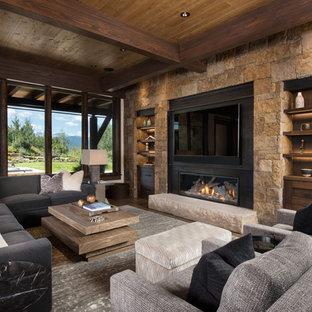 Cette image montre une grande salle de séjour chalet ouverte avec un bar de salon, un mur beige, un sol en bois brun, un manteau de cheminée en métal, un téléviseur fixé au mur, un sol marron et une cheminée ribbon.