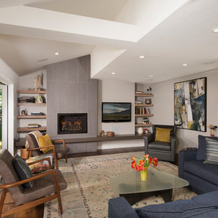 Example of a transitional open concept medium tone wood floor and brown floor family room library design in San Francisco with beige walls, a wood stove, a tile fireplace and a wall-mounted tv