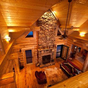 他の地域の小さいラスティックスタイルのおしゃれなファミリールーム (淡色無垢フローリング、標準型暖炉、石材の暖炉まわり) の写真