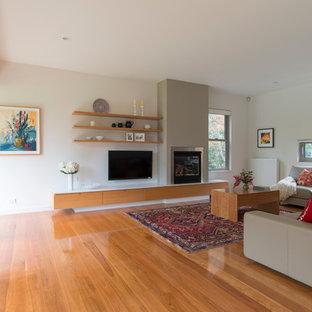 ウーロンゴンの大きいコンテンポラリースタイルのおしゃれなオープンリビング (壁掛け型テレビ、白い壁、淡色無垢フローリング、薪ストーブ、レンガの暖炉まわり) の写真