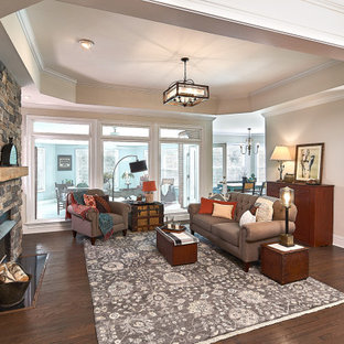 Inspiration for a mid-sized country open concept dark wood floor and brown floor family room remodel in Charlotte with beige walls, a standard fireplace, a stone fireplace and no tv