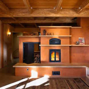 Diseño de sala de estar abierta, campestre, de tamaño medio, con paredes rosas, suelo de cemento, chimenea tradicional y marco de chimenea de yeso