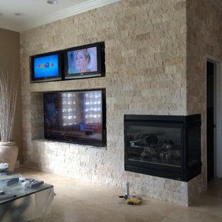 Esempio di un soggiorno classico di medie dimensioni e chiuso con pareti beige, pavimento in pietra calcarea, camino ad angolo, cornice del camino in pietra, TV a parete e pavimento beige