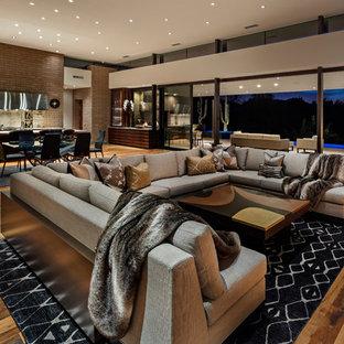 フェニックスの広いコンテンポラリースタイルのおしゃれなオープンリビング (茶色い壁、無垢フローリング、薪ストーブ、コンクリートの暖炉まわり、壁掛け型テレビ、マルチカラーの床) の写真