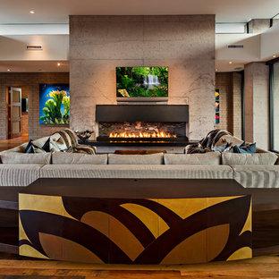 フェニックスの広いサンタフェスタイルのおしゃれなオープンリビング (グレーの壁、無垢フローリング、横長型暖炉、コンクリートの暖炉まわり、壁掛け型テレビ、マルチカラーの床) の写真