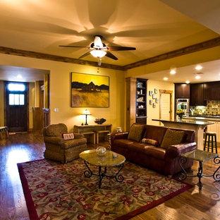 Idee per un soggiorno american style di medie dimensioni e aperto con pareti gialle, pavimento in legno massello medio, nessuna TV, nessun camino e pavimento marrone