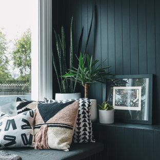 Esempio di un soggiorno contemporaneo con pareti nere, pavimento in legno verniciato, stufa a legna, cornice del camino in metallo, pavimento rosa e boiserie