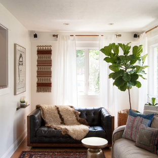 Example of a small eclectic medium tone wood floor family room design in Cleveland with white walls