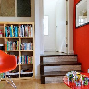 Exemple d'une salle de séjour avec une bibliothèque ou un coin lecture chic avec un mur orange et un sol en bois brun.