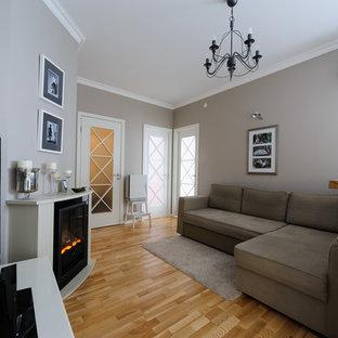 Modelo de sala de estar abierta, clásica, pequeña, con suelo de madera clara, chimenea tradicional, televisor independiente y paredes grises